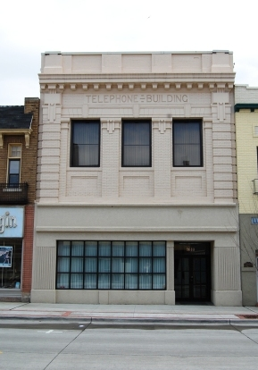 two story commercial storefront in painted brick with classical details